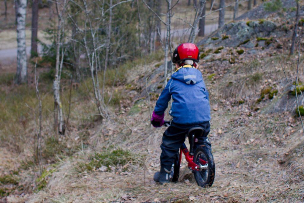 Pieni potkupyöräilijä metsässä