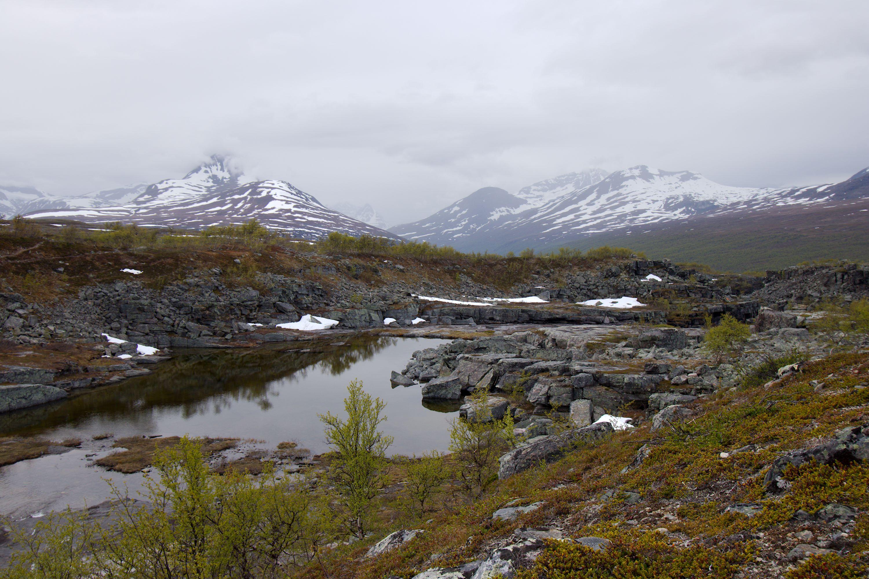 Kivikkoinen jokiuoma, taustalla lumihuippuiset tunturit