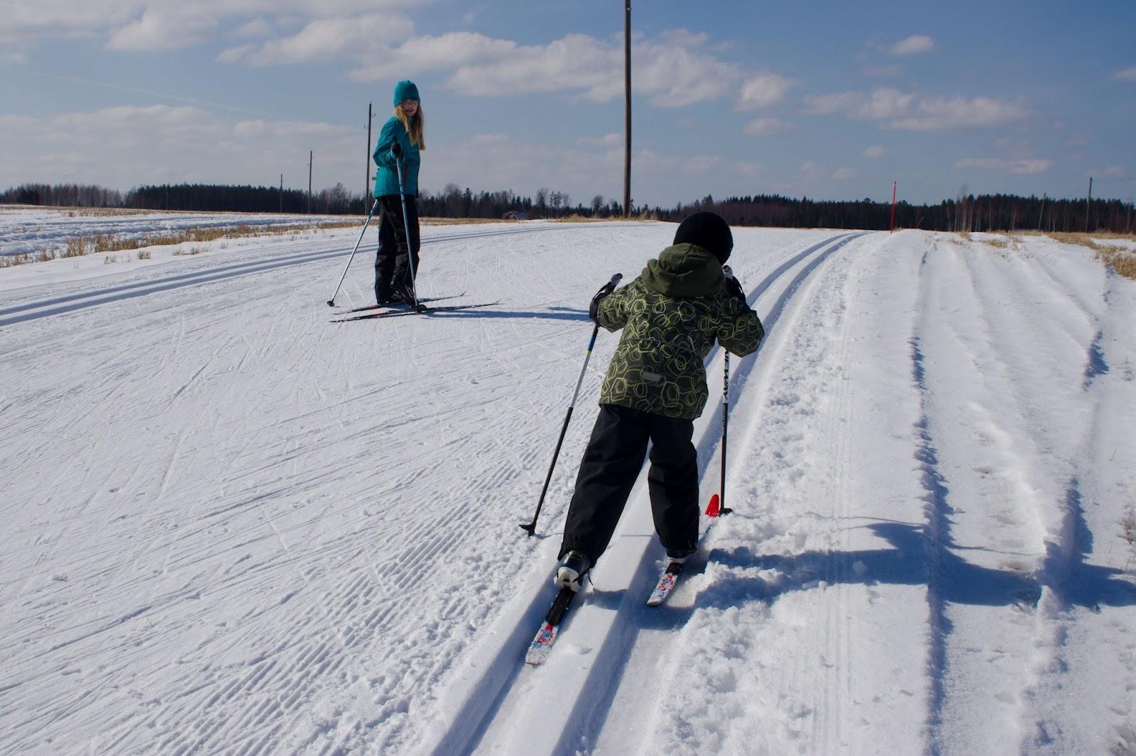 Lapset hiihtämässä latumajalta lähtevää latua