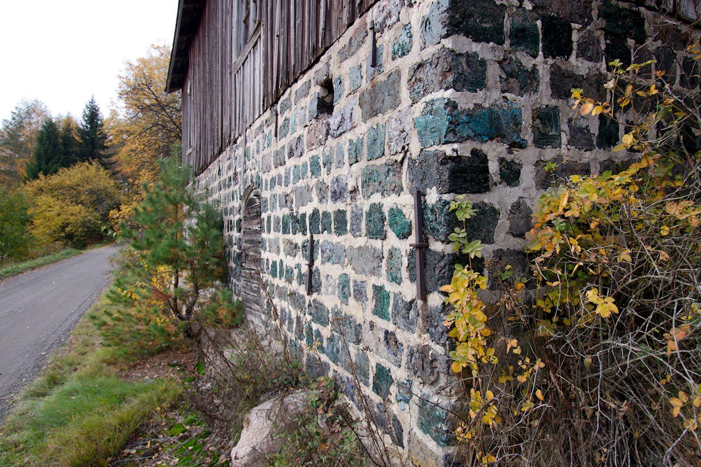 Vanhan talon kivijalka, jonka kivet hohtavat vihreinä