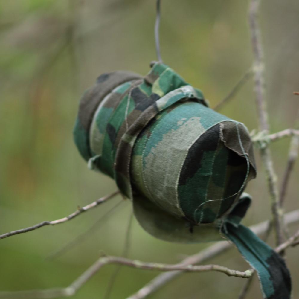 Maastokuviolla camottu geokätkö puussa roikkumassa