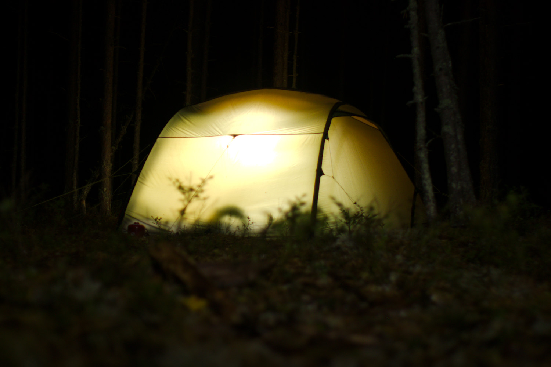 Valaistu teltta pimeässä metsässä